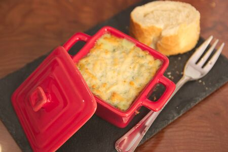 Closeup of a plate of a small red casserole with gratin food next to which we have a fork and a piece of bread all on a rustic slate plate Stok Fotoğraf