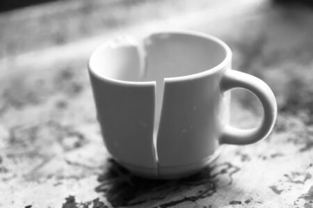 A cup of coffee that stands up despite being completely broken is on a stained surface Stok Fotoğraf