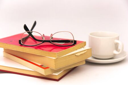 Image of some books on which there are reading glasses next to an infusion cup all isolated on white background
