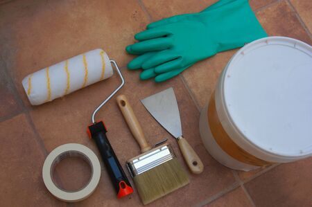 Flat lay of set of elements related to painting and decoration of the house, such as a brush, a pot of paint, gloves, a curler, a pallet and body tape on the floor