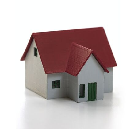 Image of a red roof miniature house isolated on white background. Conceptual image about buying and selling houses Stok Fotoğraf