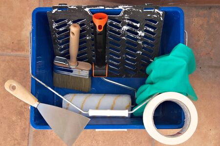Top view of a paint bucket in which there is a painter's brush and roller, along with gloves and a scraper to carry out the decoration work