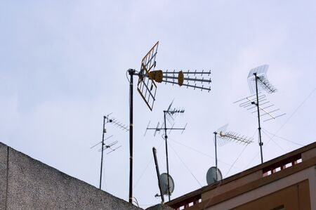 Some digital terrestrial television (DTT) antennas along with older ones and some satellite dishes, on the roofs of buildings with space for texts in the evening sky Stockfoto