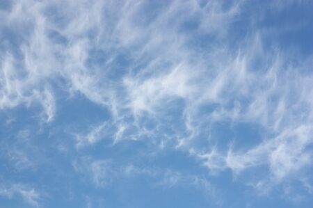 Image of a few separate clouds that form white and fibrous filaments called Cirrus on the blue sky that announce the good weather