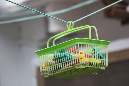 A basket for clothespins suspended from the thread where the clothes are hung for drying in the sun Фото со стока