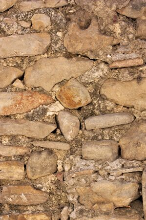 Close-up of an old wall made up of bricks and stones joined together in a rudimentary way without forming a concrete pattern