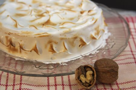 Closeup of a walnut pie and decorated with burnt meringue next to an open walnut