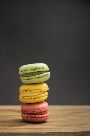 A stack of macarons of different flavors and colors on a wooden table with dark background, side light and copy space