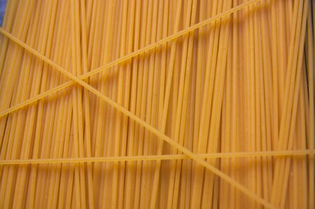 Dried egg spaghetti form a texture with a vertical line pattern useful for gastronomic backgrounds