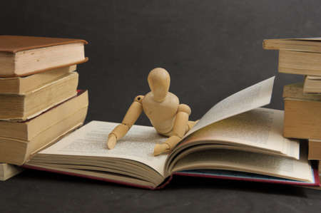 Scene of a wooden mannequin lying on a book as if reading while surrounded by other books on the right and left