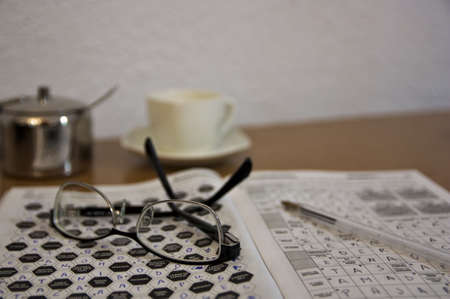 Close-up of some reading glasses and some crosswords that someone does as a hobby while having a coffee