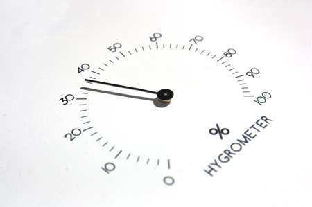 Image of an analog hygrometer in which the black needles stand out against the white background