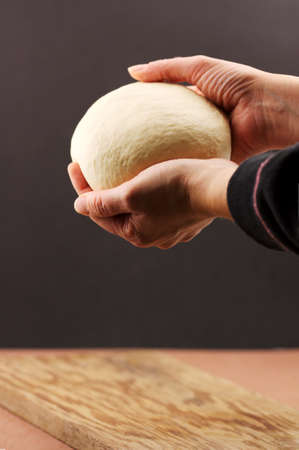 A woman holds in her hands the dough ball that she has kneaded on dark background