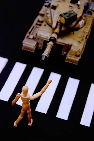 A wooden mannequin stops a military tank driving down a street in a sign in favor of non-violence. Pacifist gesture