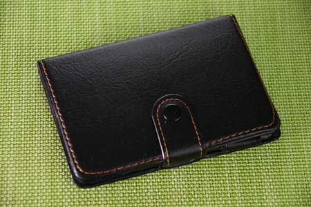 Black leather notebook on green background