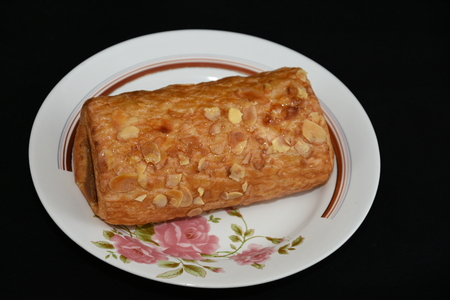 Strudel with caramel and garnished with almond flakes