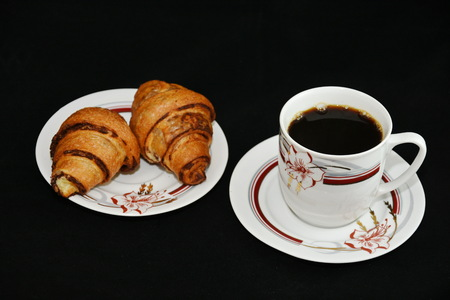 Breakfast - porcelain platter with Croissants, donuts, crullers and a cup of coffee on black background