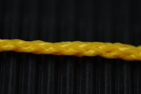 closeup photo of yellow plastic cord on black background Stock Photo