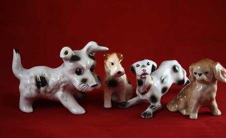 vier porseleinen honden op een rode achtergrond Stockfoto