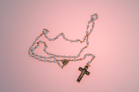 Rosary on pink background Foto de archivo - 104572449