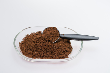 Ground coffee in glass bowl isolated on a white background