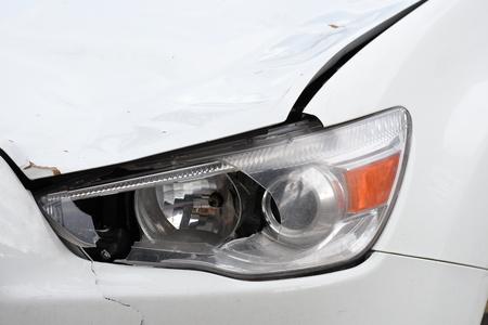 broken car headlamp  on a white car
