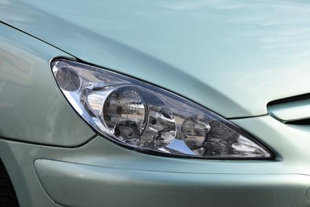 shiny headlight on a green  car