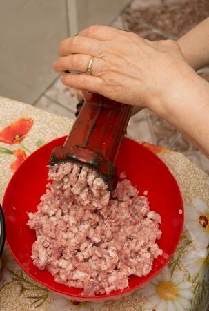 Meat grinder - process of grinding meat. Beef mince in mincing-machine. Cooking food
