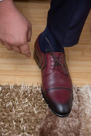 The groom is tying his shoelaces on his new black shoes