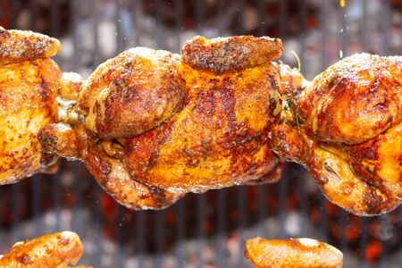 Roasted chickens on spit grilled over fire of a big barbecue