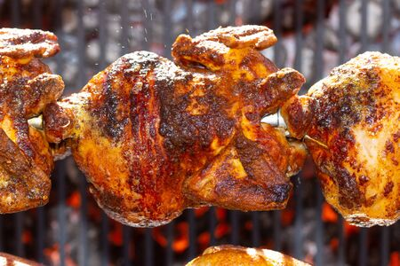 Roasted chickens on spit grilled over fire of a big barbecue,