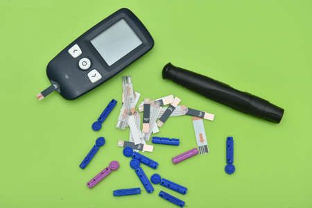 2 Diabetes set with glucometer, lancet, spare needles on green background 스톡 콘텐츠 - 150844973