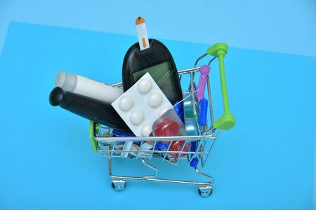 Shopping cart with lancet pen and syringes and pills, medicines