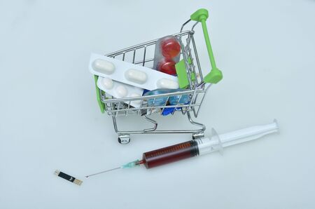Shopping cart with syringes and pills, medicines Stock Photo