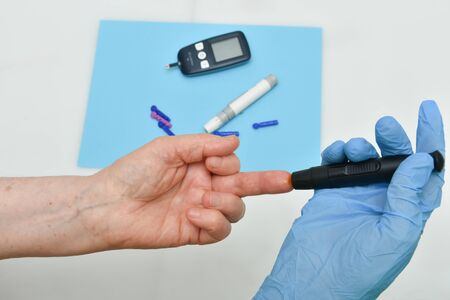 Close up of woman hands using black lancet on finger to check blood sugar level .Diabetes patients could check their blood glucose levels without a finger prick