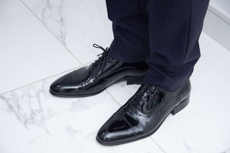 the groom closes his shoes on the wedding day