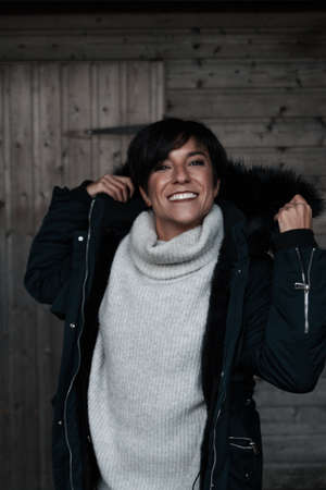 Cheerful woman wearing winter clothes putting her hood on while smiling at camera with a perfect smile