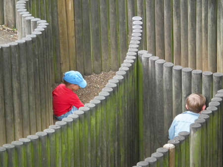 Kids playing hide and seek in a wooden labyrinth
