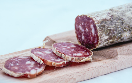 close up of a cutting board with italian salame on white background