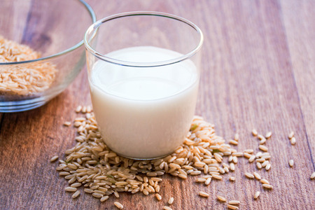 glass of rice milk and a bowl of brown rice Imagens