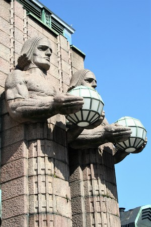 deatil: deatil of facade of central railway station at Helsinki, with  pairs of statues holding spherical lamps, in art nouveau style Stock Photo