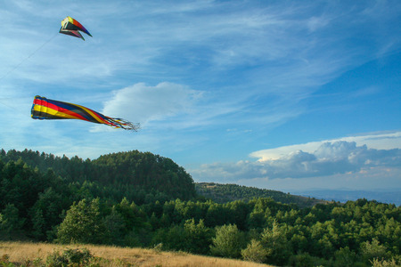 weightless: multicolored kite flying on the background of a blue sky
