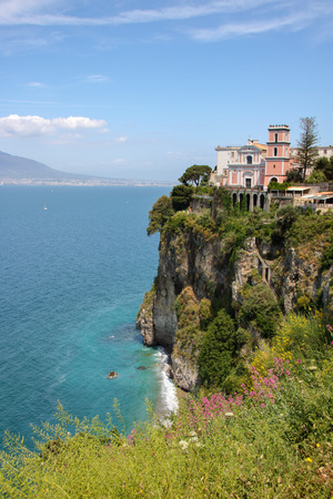 Scenic view of Vico Equense with the church of Santissima Annunziata on the cliff over the sea, mount Vesuvius on background, in Sorrento's peninsula, Naples province, Italy Stock Photo
