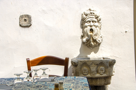 table of a typical restaurant  near a old fountain in the historic center of Amalfi, Italy