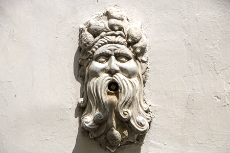 head of a fountain representing a human face in the old center of Amalfi, Italy
