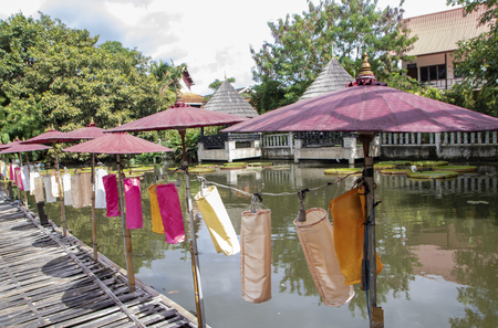 Bamboo footbridge with paper umbrellas and lanterns in the garden of the buddhist temple Wat Chang Taem, Chiang Mai, Thailand 免版税图像