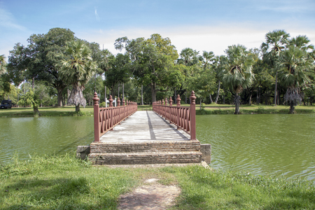 red wooden bridge over channel in Sukhothai historical park in Thailand