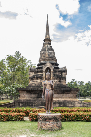 Walking buddha statue in Wat Sa Si, Buddhist temple in historical park of Sukhothai, Thailand