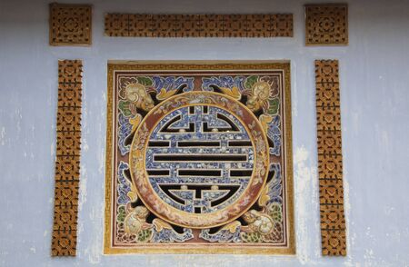 Decorated window in the Imperial City (Vietnamese: Hoàng thành), the  walled enclosure within the citadel (Kinh thành) of the city of Huế, the former imperial capital of Vietnam