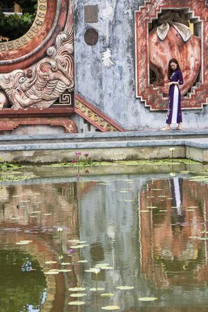 At Hoi An, Vietnam , on august 2019 -  Girl reflecting in the fountain of Tam Quan gate, or three-entrance gate, leading  to the old temple complex built in 1626 and known as Ba Mu Temple